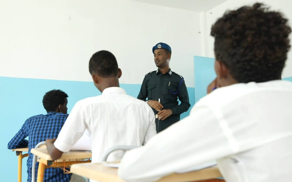 Police officer proctoring students sitting for an exam.